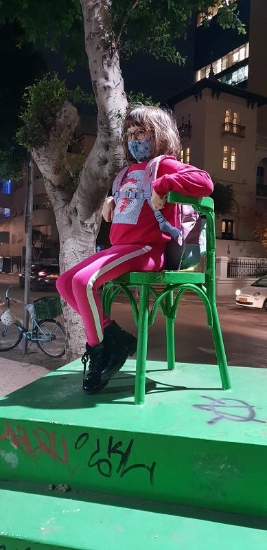 ילדה יושבת על כסא ירוק ונראית עצלנית