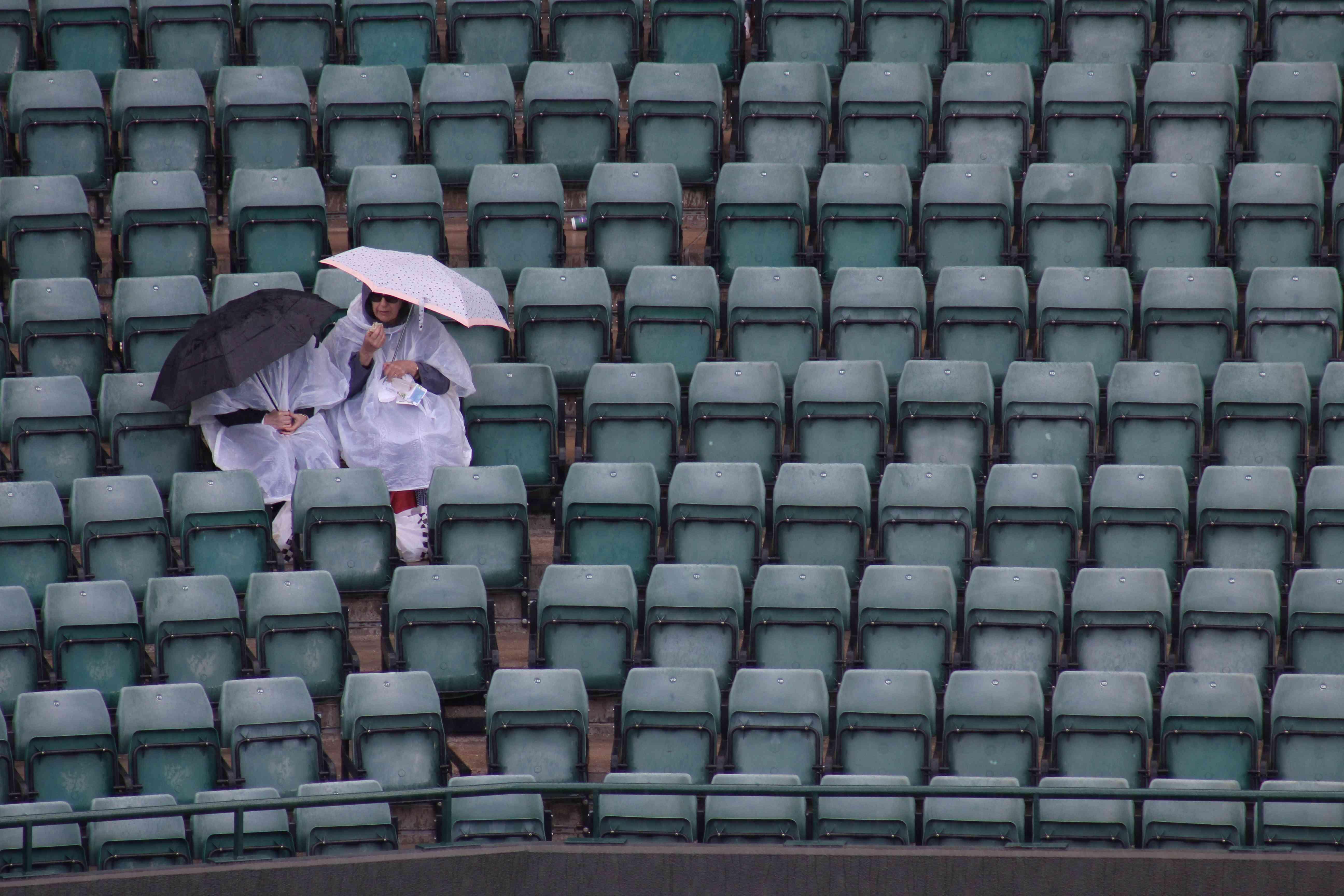 Wimbledon 2 ladies sitting with brollies
