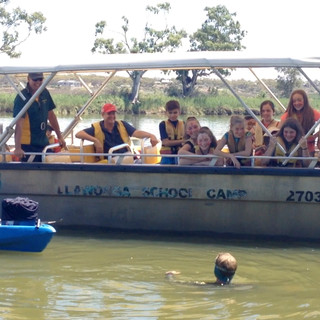Hunter and Cydney talk with a group of school kids on a river field trip