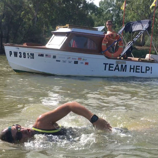 Hunter Helmick swims while Tuck Helmick pilots the Team Help boat.