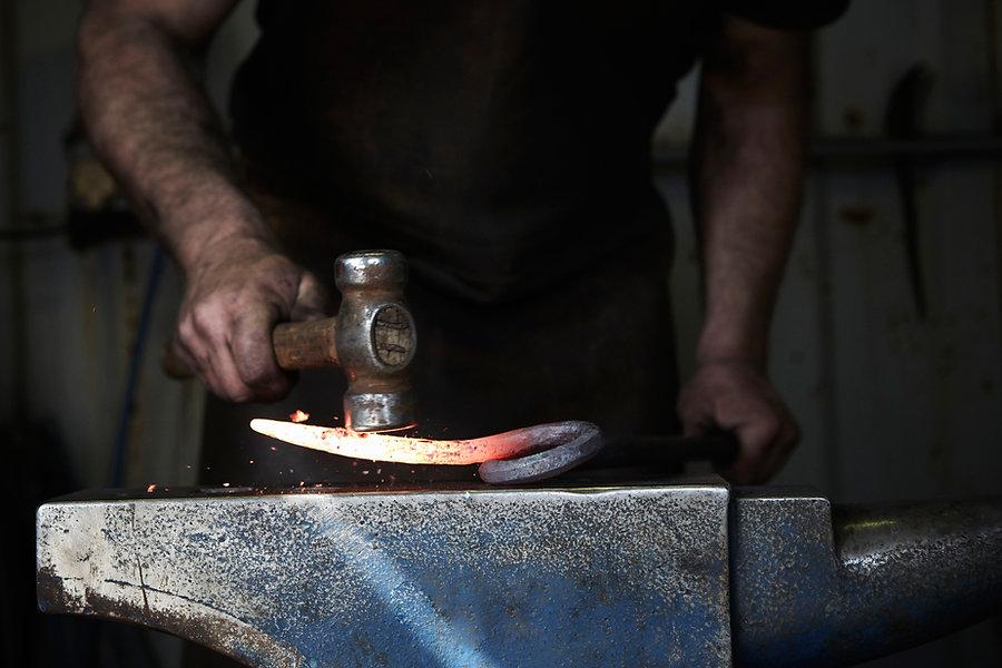 Metallbauer schmiedet eine Eisenstange