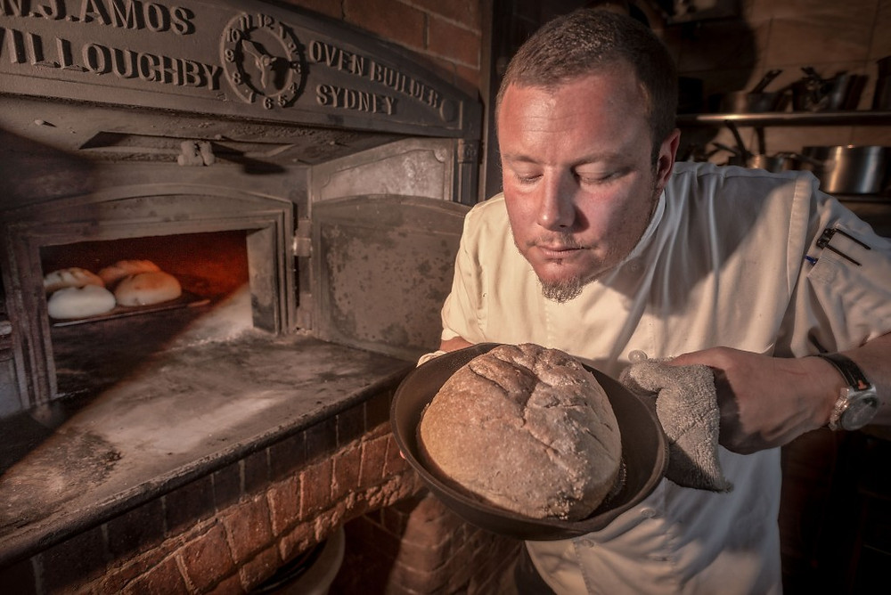 Vesta chef Misha Laurent checks a loaf he has baked in the antique woodfired oven