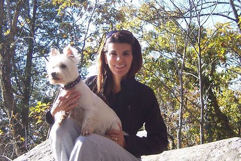 Kristine as an adult holding her westie dog