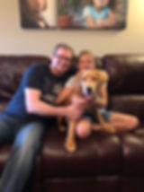 Dog training client family with dog on sitting on couching