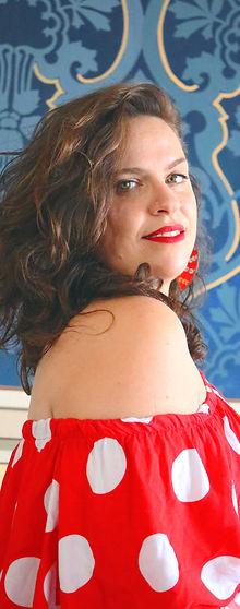 Milka, roupa vermelha com bolas brancas. Ao fundo uma parede azul com branco