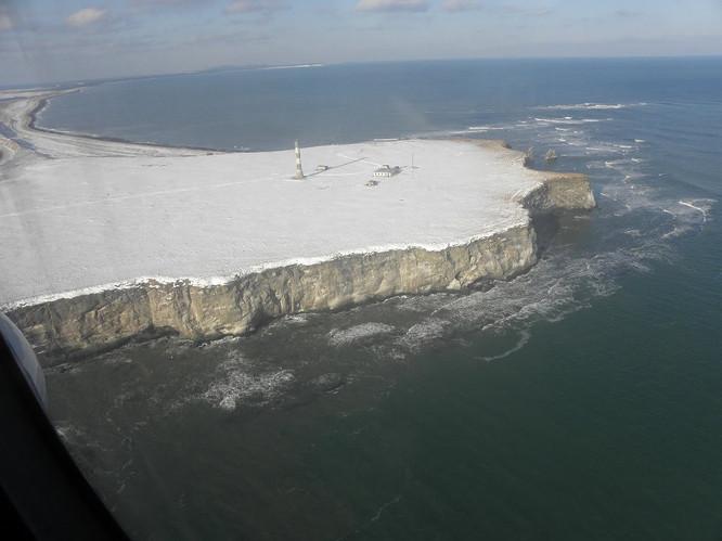 Terpeniya Lighthouse 24 декабря 1954 года в Извещении мореплавателям ГС ТОФ № 42 часть II было объявлено об установке маяка Терпения на мысе того же названия. Огонь маяка белый круговой группо-проблесковый: свет 1,2 сек + темн. 5,8 сек + свет 1,2 сек + темн. 21,8 сек – период 30 сек – 4 проблеска в минуту. Дальность видимости огня 22 мили (41 км). Высота центра огня от планировочной поверхности 37,40 м,  от уровня моря 71,40 м. Башня маяка цилиндрическая, железобетонная с чёрными и белыми горизонтальными полосами и с фонарным сооружением. Башня установлена на 8-гранном пирамидальном цоколе. Высота маяка 41,20 м. Прежний штатный огонь Терпения сохранялся как резервный. 25 августа 1955 года было объявлено в Извещении мореплавателям ГС ТОФ №181 часть II об изменении характера огня маяка на проблесковый: свет 3 сек + темн. 4,5 сек – период 7,5 сек – 8 проблесков в минуту. Этот характер огня сохраняется до сих пор.