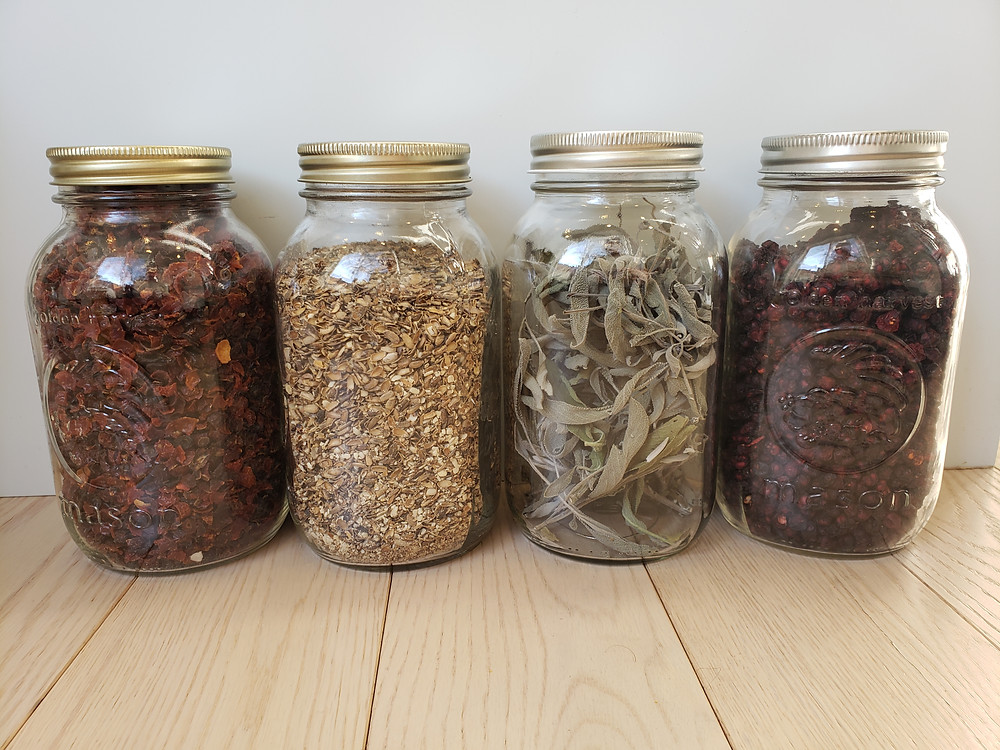 Four jars of loose herbs - rosehips, ginger, sage and schisandra