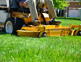 person on riding lawn mower, mowing grass