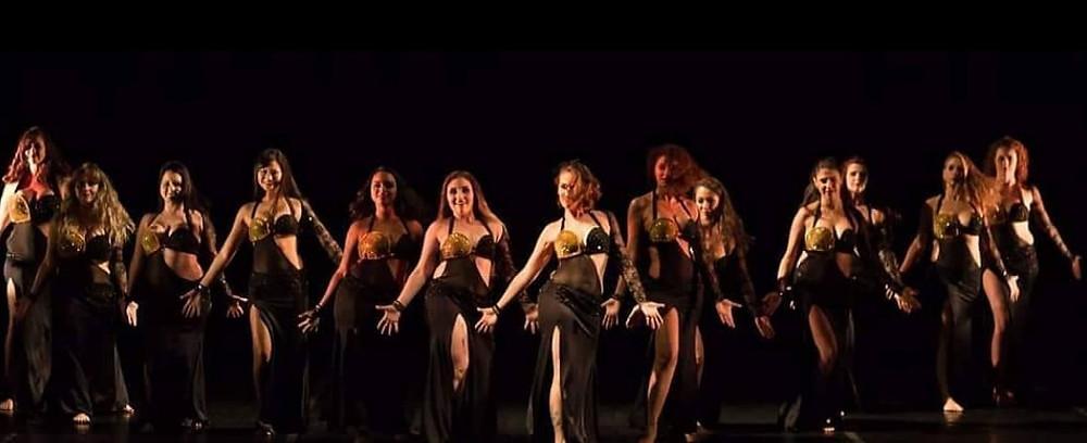 Cia Erica Seccato em Apresentação de palco. Todas as bailarinas vestidas com figurino preto e dourado.