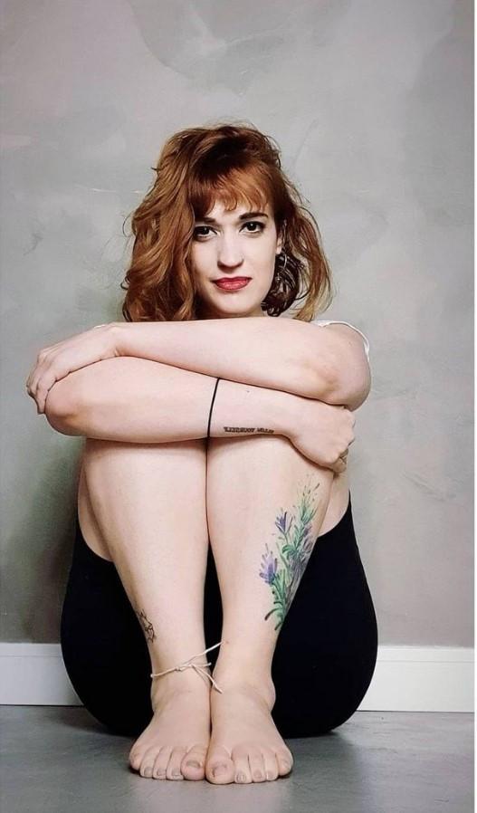 Bailarina Erica Seccato sentada no chão abraçando os joelhos.