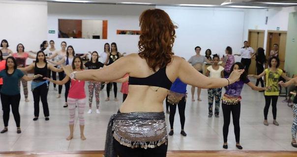 Aula Dança do Ventre Iniciante presencial com professora de costas e váriaspessoas assistindo a aula e realizando o exercício proposto.