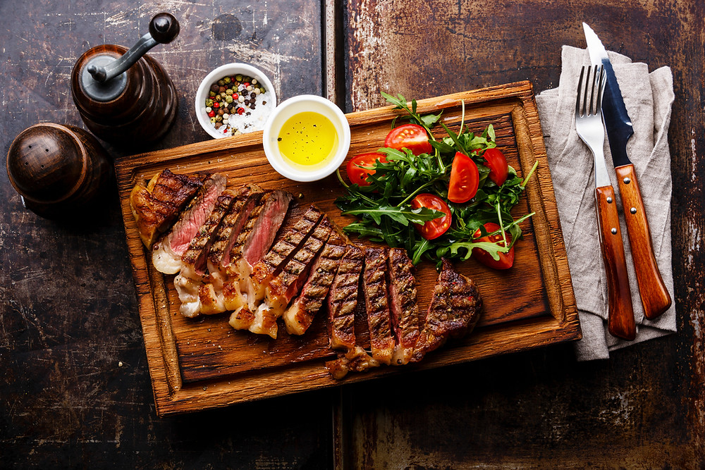 Image of steak and arugula and tomato salad on a wooden chopping board.