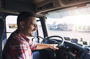 Smiling truck driver in the truck cabin..jpg