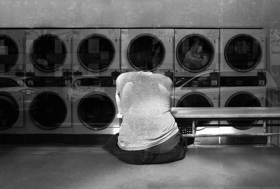 Mann sitzt in Wäscherei und senkt den Kopf - Streetfotografie in Köln - Streetphotography Cologne - Christopher Reuter - wie man als Künstler aus einem kreativen Loch kommt.