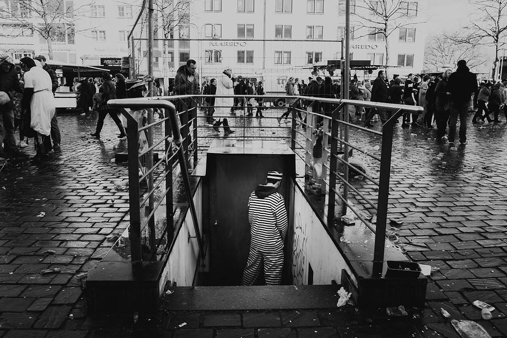 Mann pinkelt gegen eine Wand - Kölner Karneval - besoffener im Kölner Karneval - Wild Winkler - Streetfotografie in Köln - Streetphotography Cologne - Christopher Reuter -Streetfotografie in Schwarz weiß