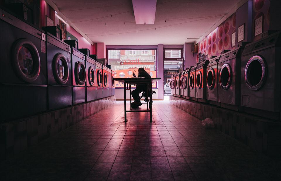 Mann sitzt in Wäscherei und senkt den Kopf - Streetfotografie in Hamburg - Streetphotography Hamburg - Christopher Reuter - wie man als Künstler aus einem kreativen Loch kommt.