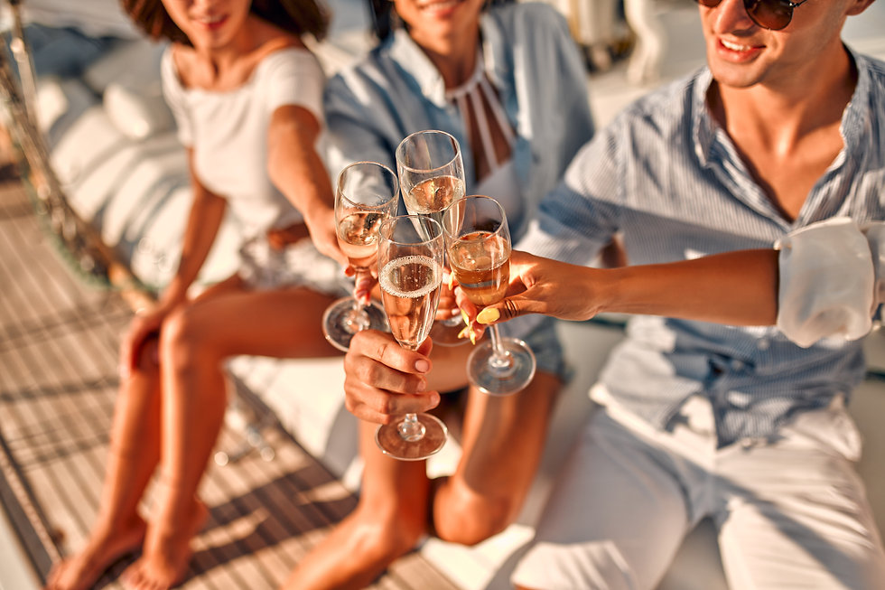 Cheers! Cropped image of group of friends relaxing on luxury yacht and drinking champagne.