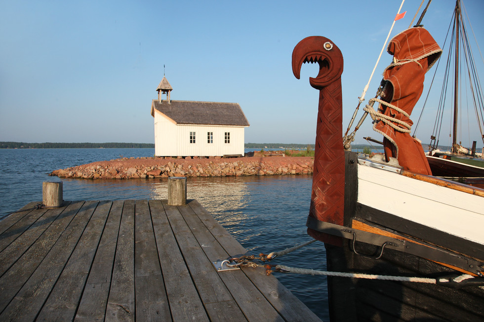 Old viking boat and white chapel in ship