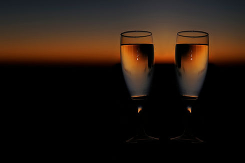 Romantic glass of champagne or wine in hand. red sunset Glasses of white wine against sund