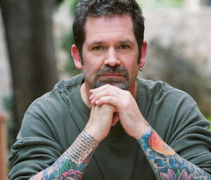 A man with tattoos looking pensive