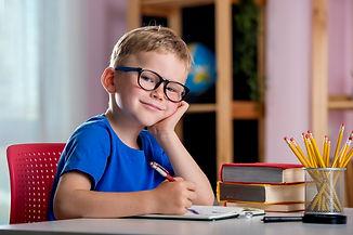 Back to school. Thinking child boy writi