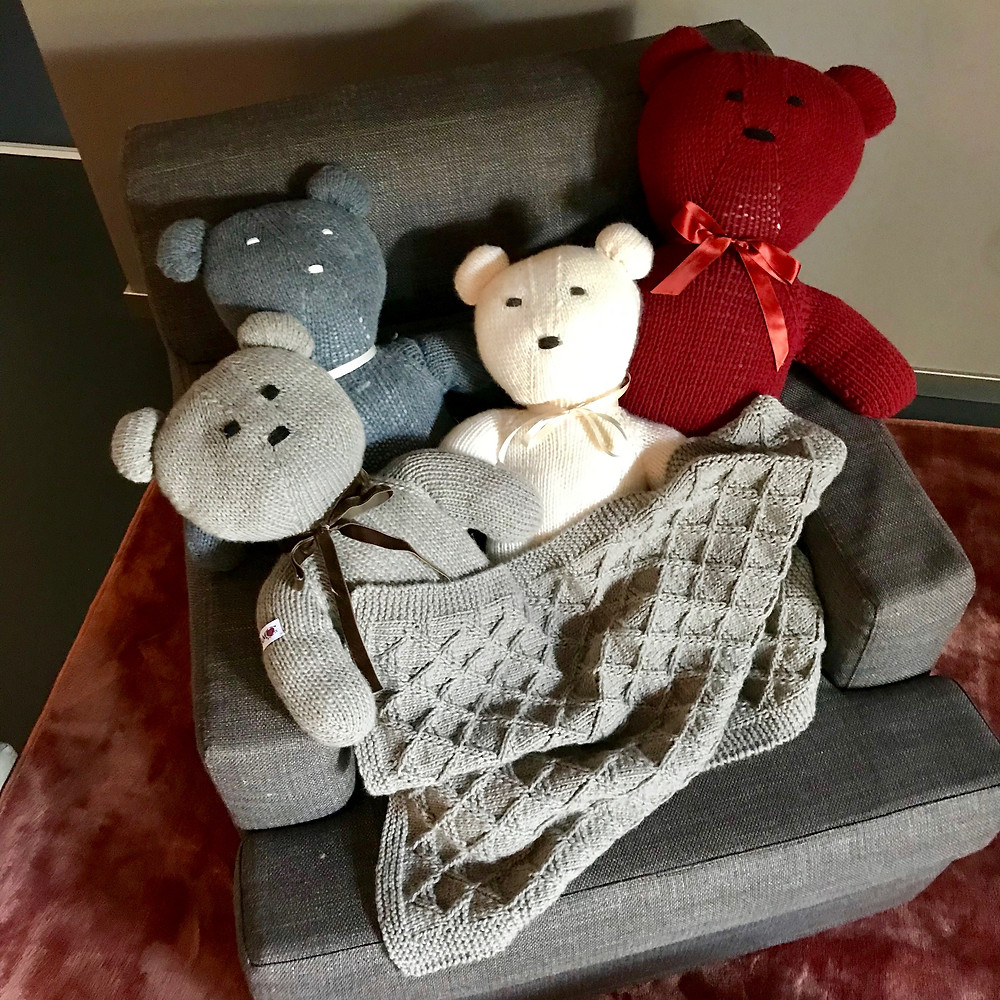 Swiss Teddybears with blanket relaxing on armchair