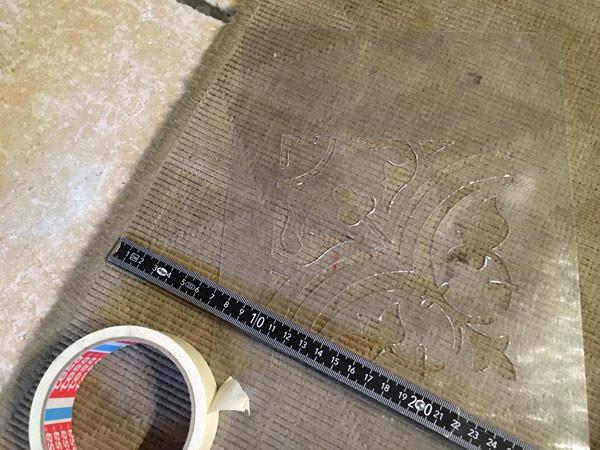 Eine Fußmatte mit Schablone bestempeln