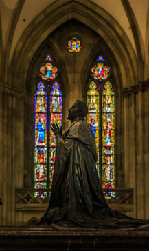 Statue in front of stained glass