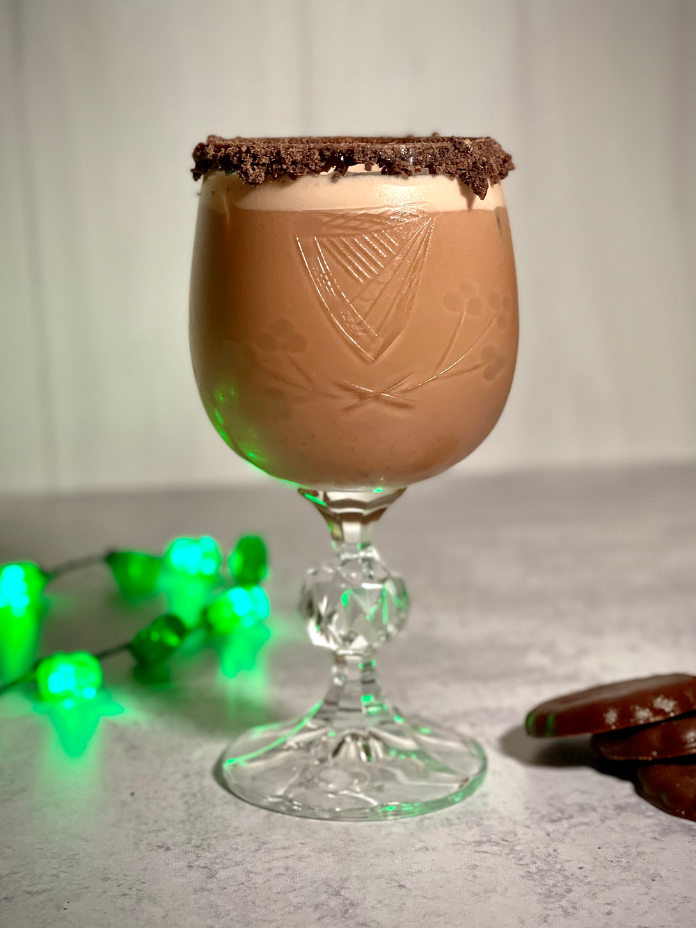 Girl Scout Cookie themed cocktail featuring vodka, thin mint cookies, cream, mint syrup and chocolate sauce. Shaken and served over ice with a thin mint cookie rim.