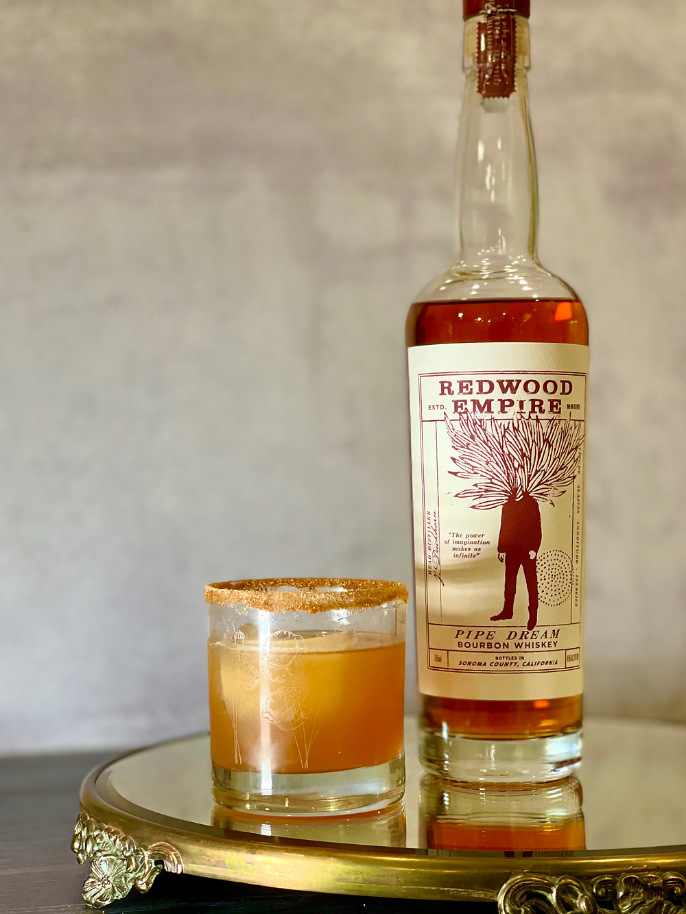 Rocks cocktail glass with spice rim filled with bourbon cocktail, next to Redwood Empire Pipe Dream Bourbon Bottle with red and white label.