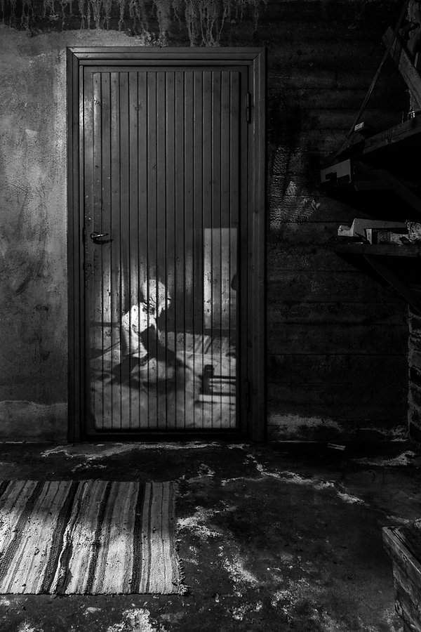 Black and white image by Minna Lehtola from the series NightHouse, long exposure, projected image combined with ambient light, a child playing on the floor