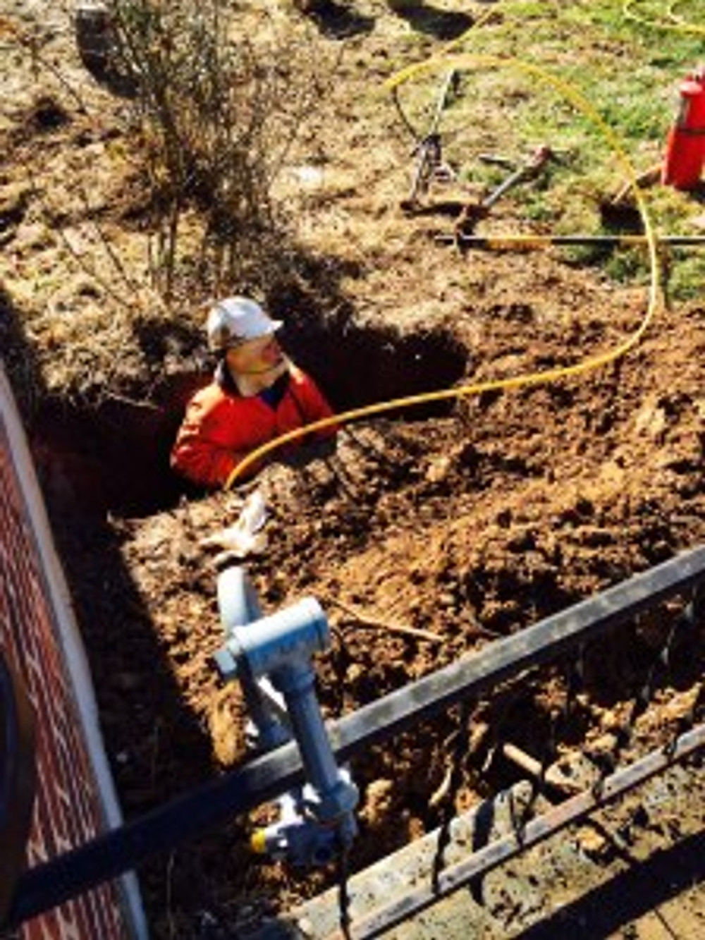 Outside  putting in the pipeline to the house. How is she going to get out of that hole?