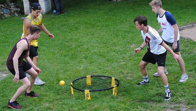 vier Jungs spielen Spikeball in dem Garten