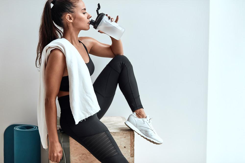 Eine Frau trinkt Wasser während des Workouts