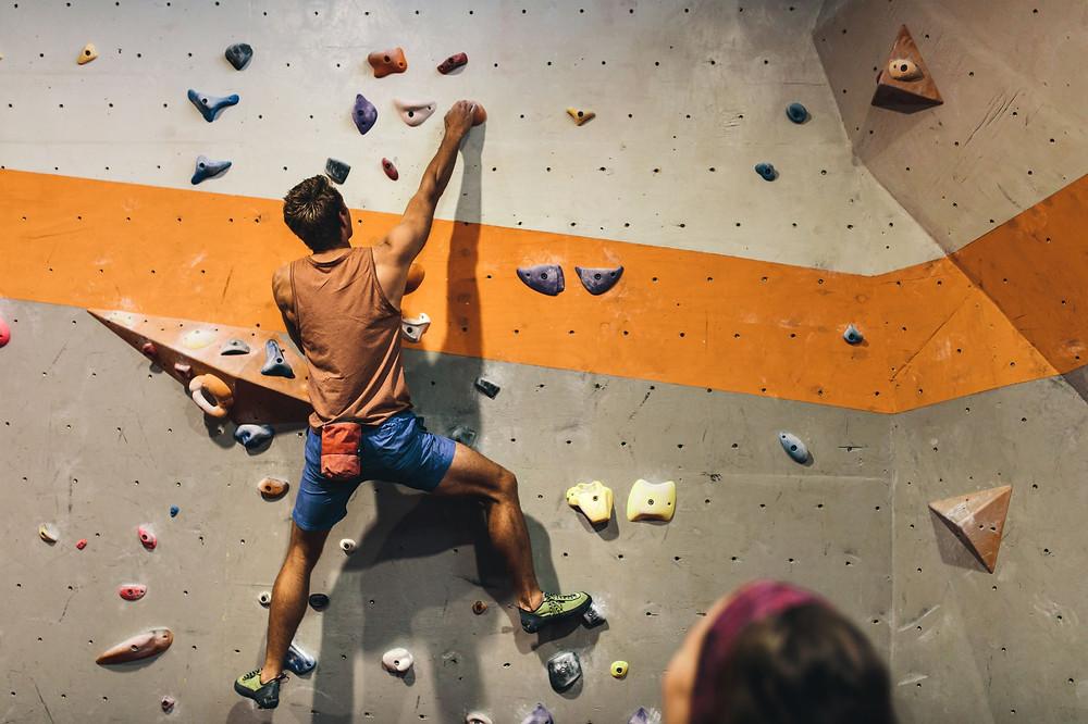 Mann bouldert an der künstlichen Kletterwand