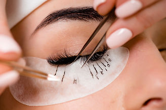 Eyelash extension procedure close up. Beautiful Woman with long lashes in a beauty salon..