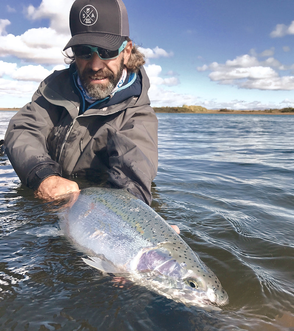 Jeff Liskay holds a chrome steelhead facing you in the water.