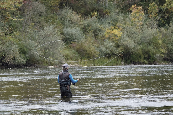 Jeff Liskay from the back doing a spey cast. The fly line is in the air in the shape of an oval