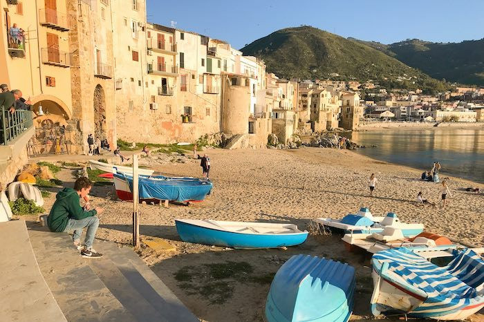 seaside village of Cefalu, Sicily with boats pulled up onto the sandy shore