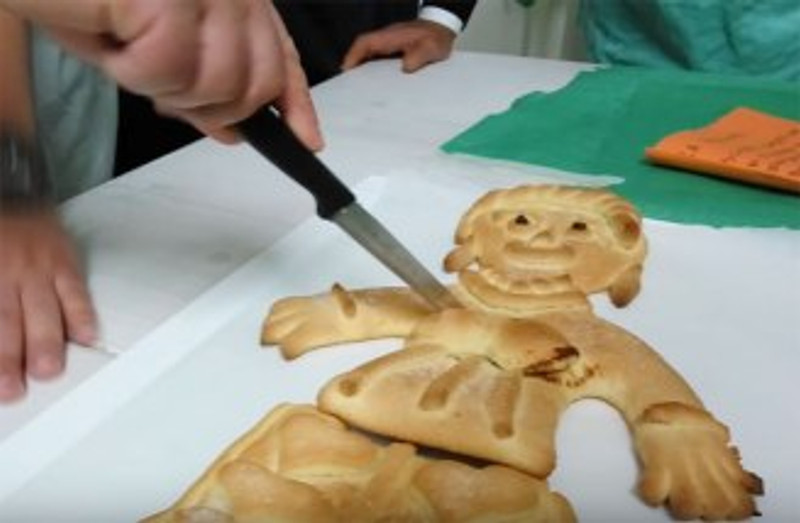Italian-cookie-in-shape-of-old-woman-being-cut-with-knife
