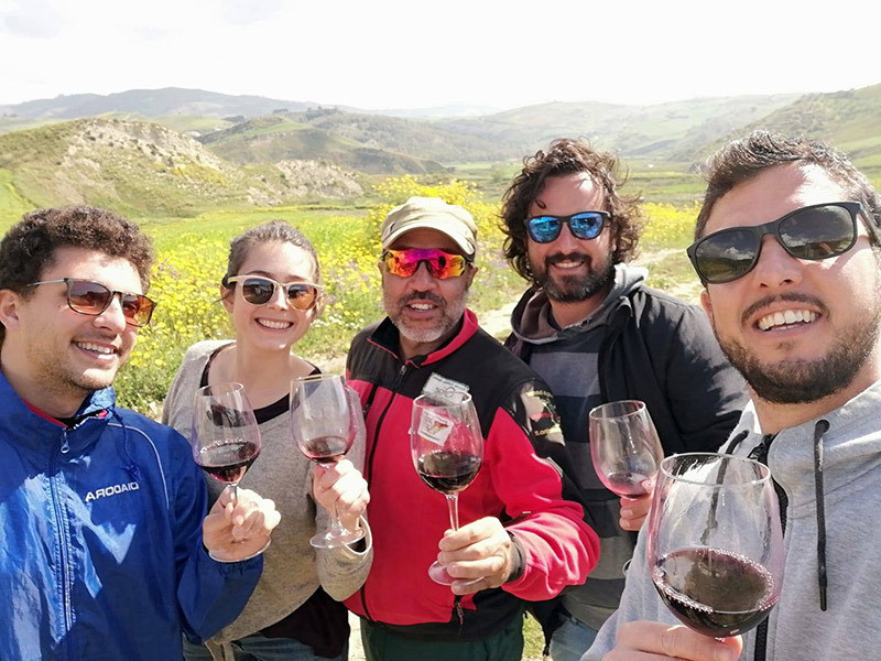 4 men and one woman in hiking clothes hold their wine glasses up while smiling, rolling hills of Sicily and wildflowers are in the background