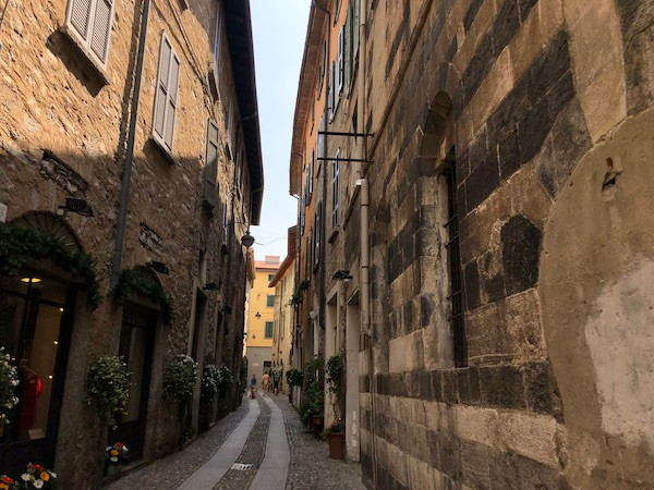 Narrow cobblestone street in Italy with tall stone buildings on either side