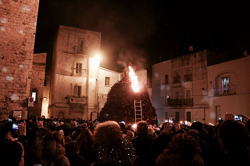 a crowd gathered around a giant bonfire in a piazza in italy which has just been lit