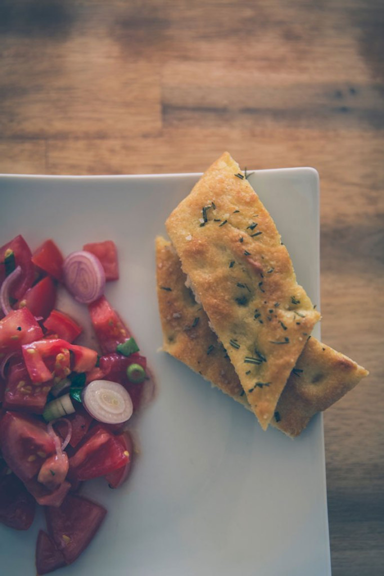 diagonal slices of italian herb focaccia on a plate next to tomato and onion bruschetta