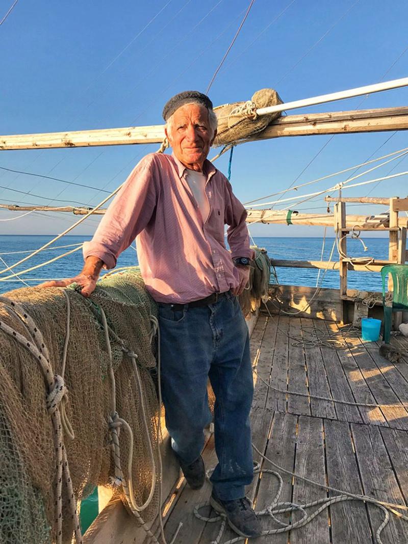old fisherman posing on his trabucco fishing machine in Gargano italy