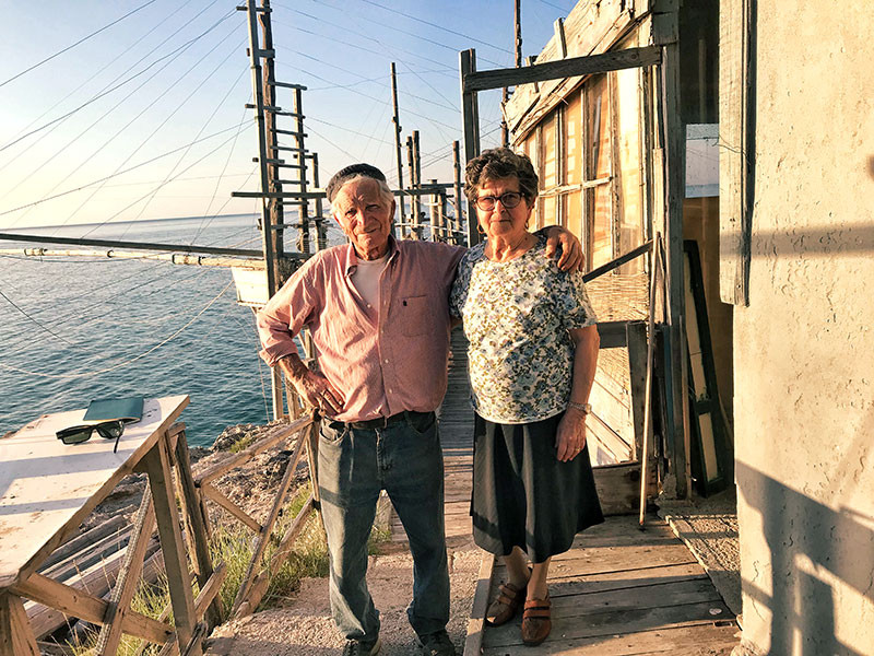 elderly couple posing in front of their trabucco in gargano italy
