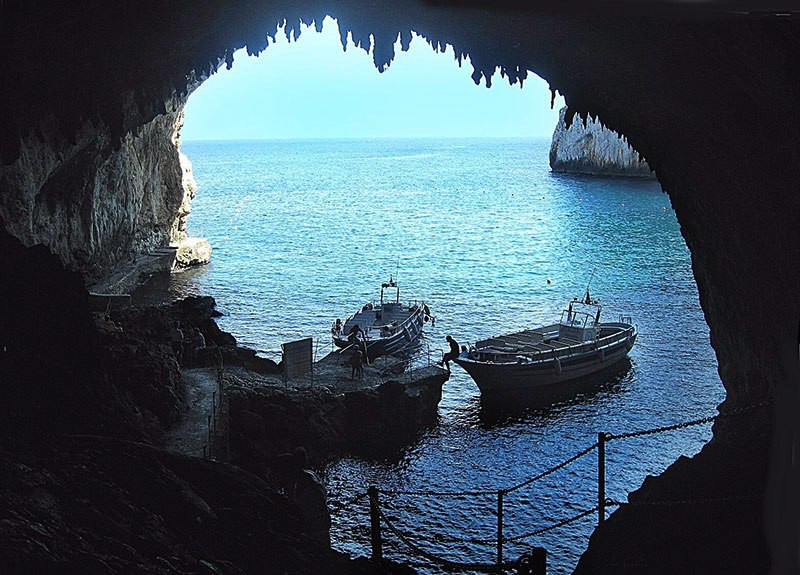 inside a sea cave in southern italy with two boats