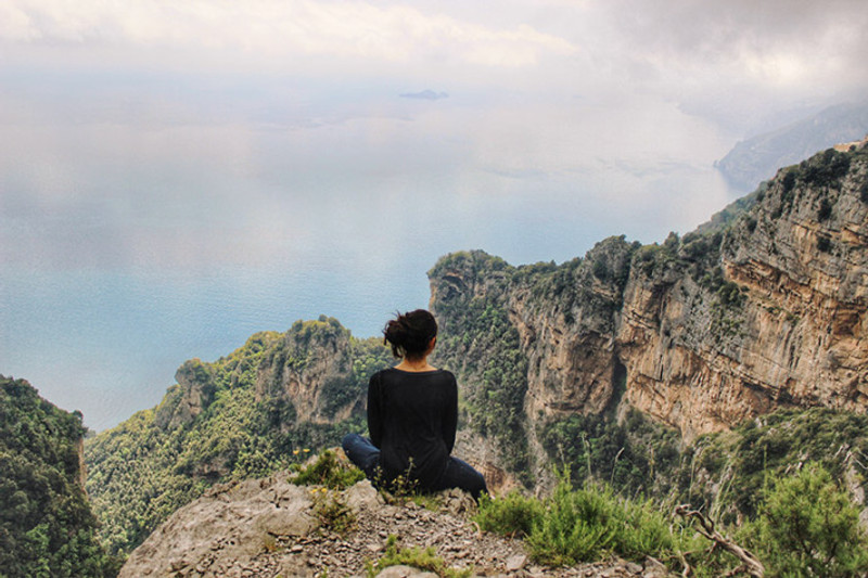 Woman sits on the edge of a cliff overlooking the Amalfi Coast in Italy