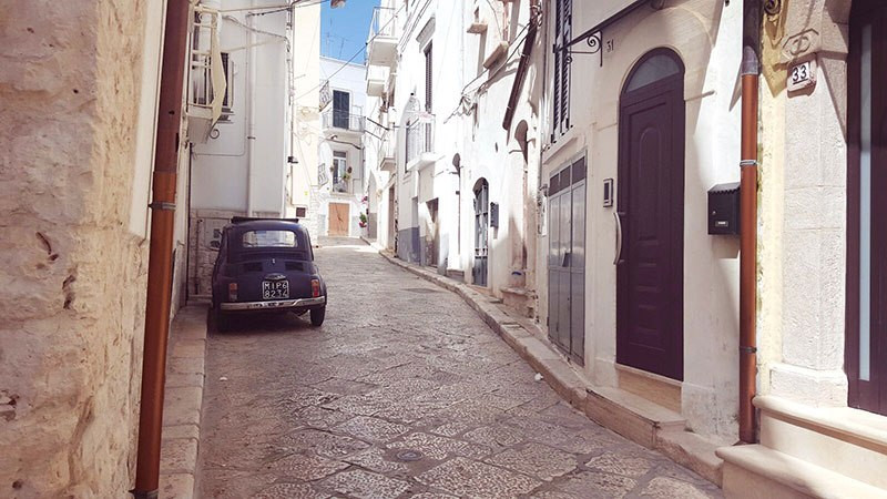 old fiat in alleyway on street of white washed village in puglia castellana grotte italy