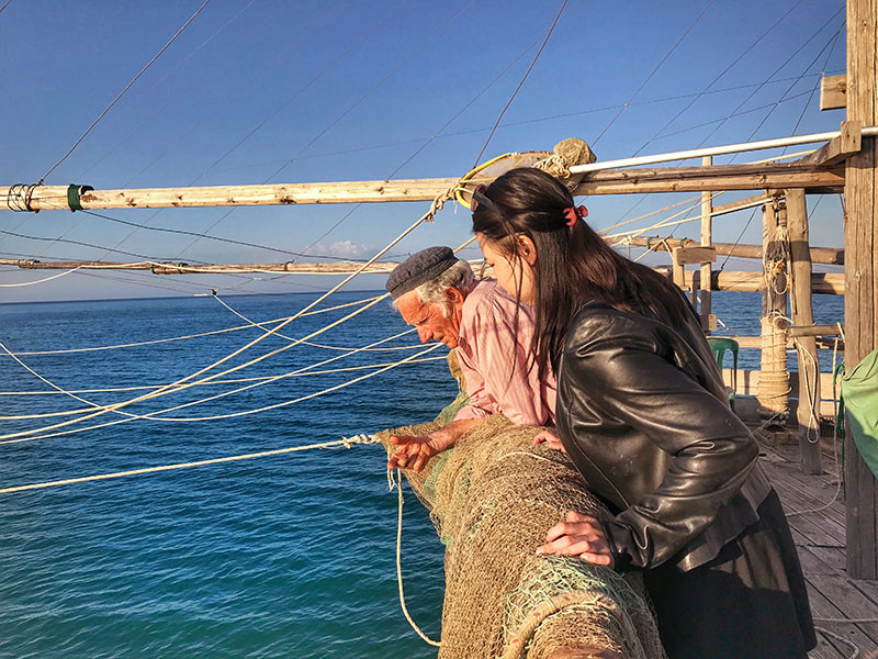 old fisherman and an asian visitor on his trabucco fishing machine in gargano italy